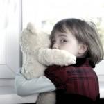Ребенок с игрушкой у окна
